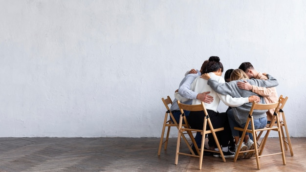 Pessoas se abraçaram em um círculo em uma sessão de terapia de grupo