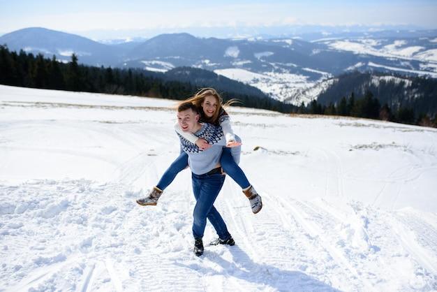 Pessoas se divertindo e correndo nas montanhas no fundo de altos picos nevados
