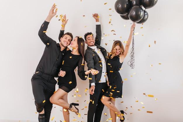 Pessoas se divertindo na festa com balões pretos e confetes