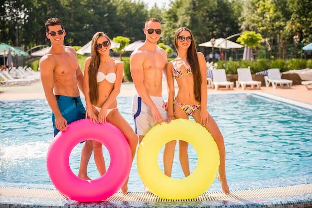 Pessoas se divertindo na piscina com anéis coloridos.