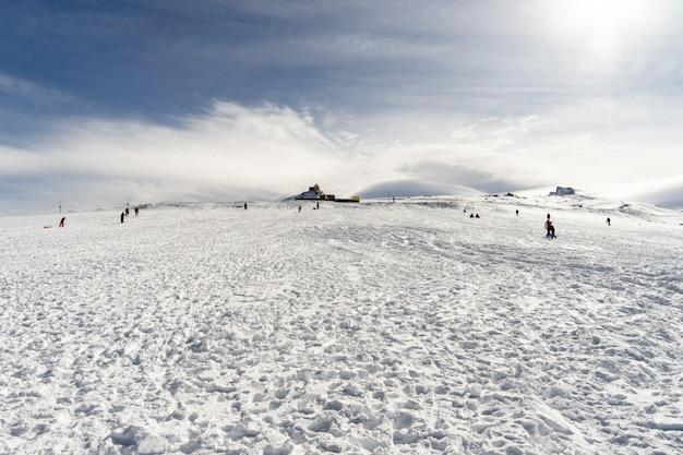 Pessoas se divertindo nas montanhas nevadas na serra nevada