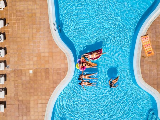 Pessoas se divertindo no verão na piscina com colchões infláveis coloridos da moda