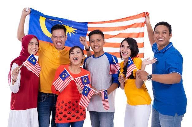 Pessoas segurando a bandeira da malásia comemorando o dia da independência