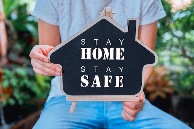 Pessoas segurando a casa de madeira com texto. ficar em casa, ficar conceito seguro. auto-quarentena e distanciamento social. novo normal e vida após covid.
