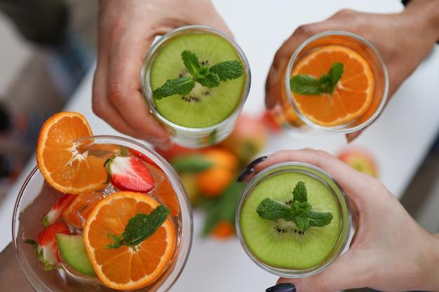 Pessoas segurando copos com bebidas de frutas brilhantes