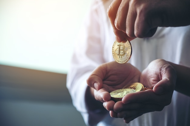 Pessoas segurando e dando bitcoin
