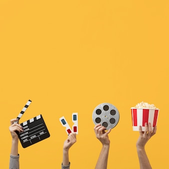 Pessoas segurando elementos do filme com espaço de cópia