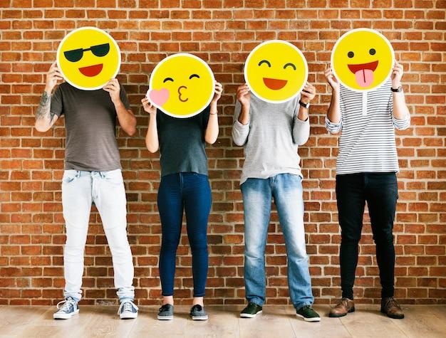 Pessoas segurando emoticons positivos
