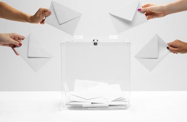 Pessoas segurando envelopes brancos prontos para colocá-los nas urnas