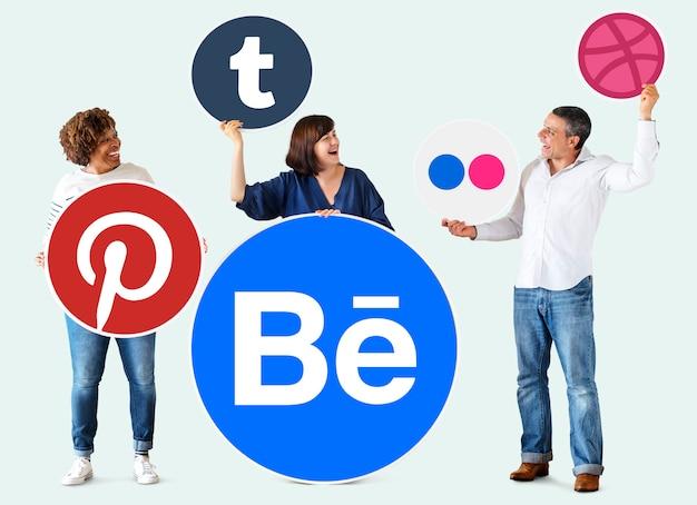 Pessoas segurando ícones de marcas digitais