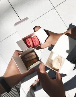 Pessoas segurando macarons na caixa