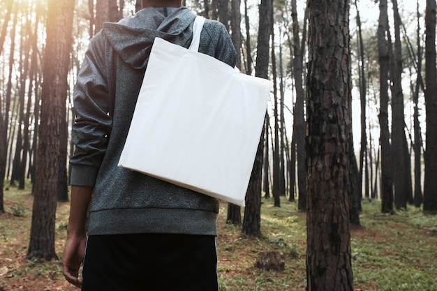 Pessoas segurando o saco de algodão para maquete em branco no fundo da natureza