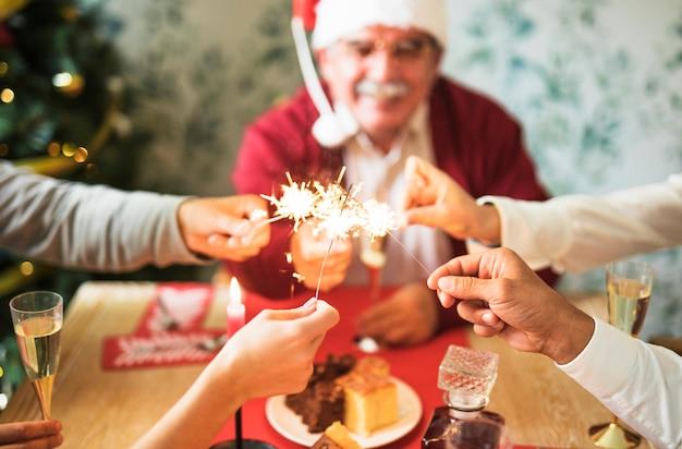 Pessoas segurando queimando fogos de bengala na mesa festiva
