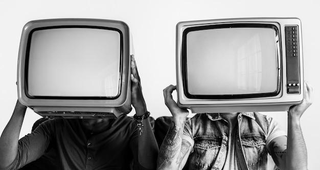 Pessoas segurando televisão retrô ao lado do outro