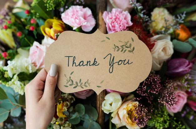 Pessoas segurando um cartão de agradecimento com fundo de buquê de flores