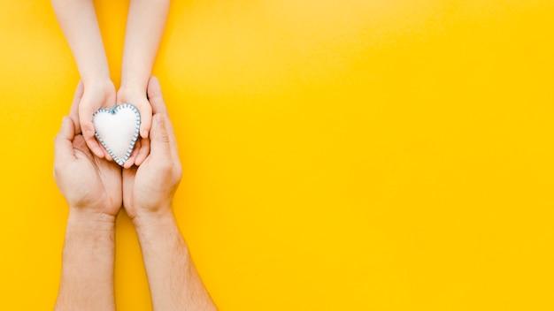 Pessoas segurando um coração branco nas mãos, com espaço de cópia