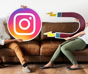 Pessoas segurando um ícone do Instagram