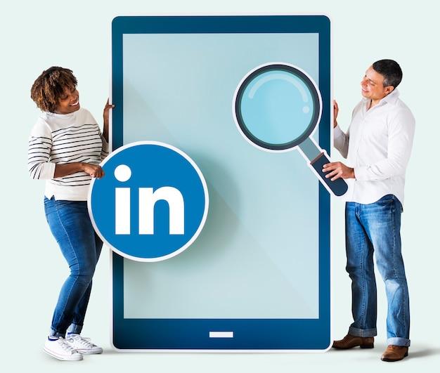 Pessoas segurando um ícone do linkedin e um tablet