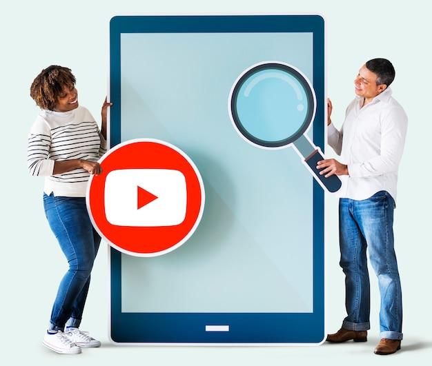 Pessoas segurando um ícone do youtube e um tablet