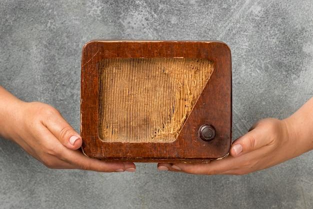 Pessoas segurando um rádio vintage