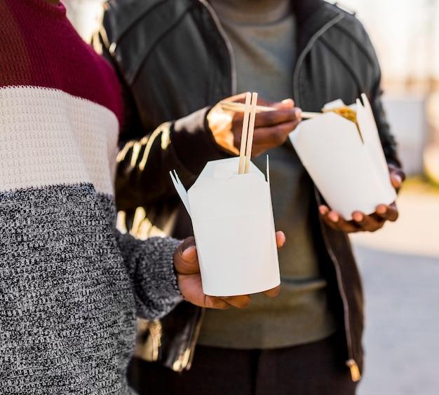 Pessoas segurando uma embalagem de comida para viagem