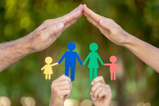 Pessoas segurando uma família de papel nas mãos