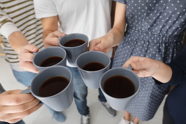 Pessoas segurando xícaras de café juntas. conceito de unidade
