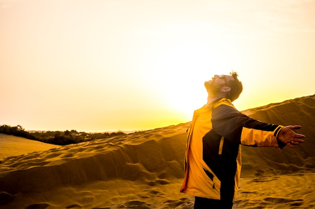 Pessoas sênior de meia idade do homem em pé com o deserto de braços abertos como o conceito de liberdade e satisfação. sol na luz de fundo e luz amarela do pôr do sol. viajante caucasiano em desejo de viajar