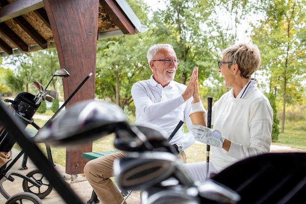 Pessoas seniores positivas, prontas para o treinamento de golfe