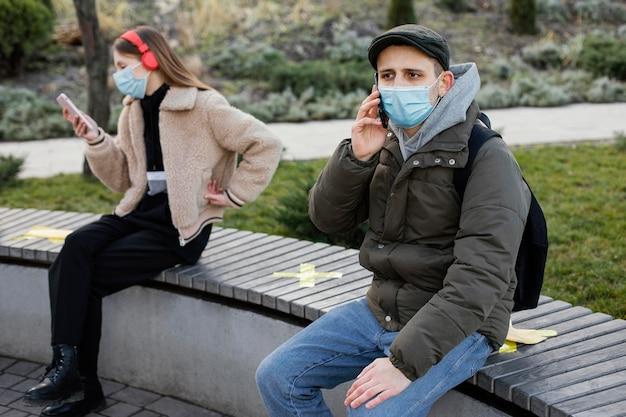 Pessoas sentadas à distância usando máscara