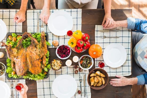 Pessoas sentadas à mesa com comida diferente