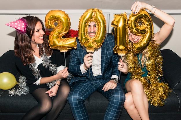 Pessoas sentadas com inscrição de 2019 de balões