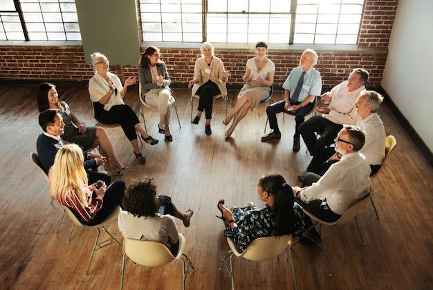 Pessoas sentadas conversando com um grupo