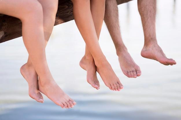 Pessoas sentadas em um deck com os pés descalços