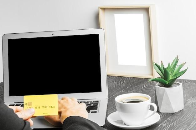 Pessoas sentadas em um trabalho com um laptop em uma mesa de madeira na superfície do quadro-negro