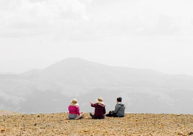 Pessoas sentadas na beira da montanha, apreciando a vista e conversando com um fundo nebuloso