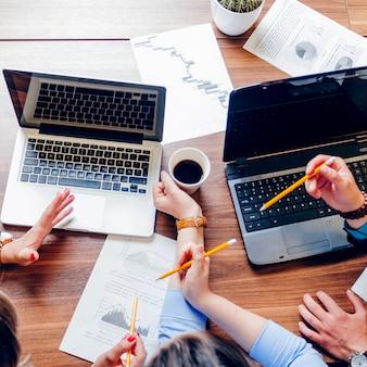 Pessoas sentadas na mesa com laptops trabalhando