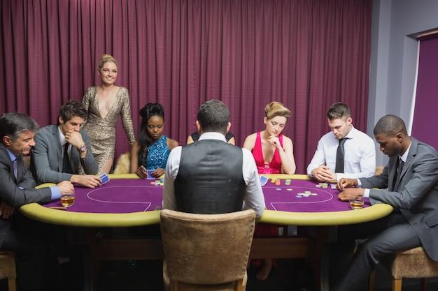Pessoas sentadas na mesa do casino com uma mulher parada