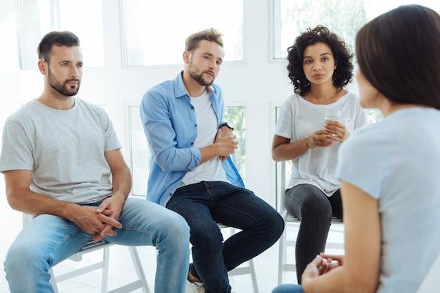 Pessoas sérias, infelizes e sombrias olhando para a amiga e ouvindo seus problemas enquanto estão prontas para consolá-la