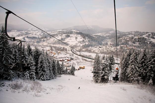 Pessoas sobem no elevador nas montanhas dos cárpatos. fechar-se. natureza do inverno. queda de neve forte. vista do topo. e olhando para baixo.