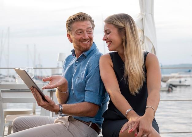 Pessoas sorridentes com tablet tiro médio