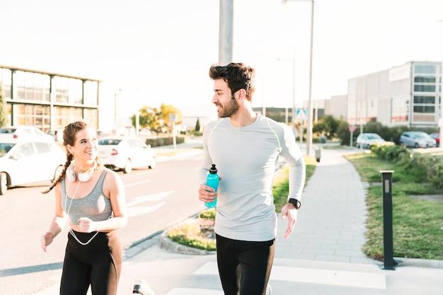Pessoas sorridentes correndo no crosswalk