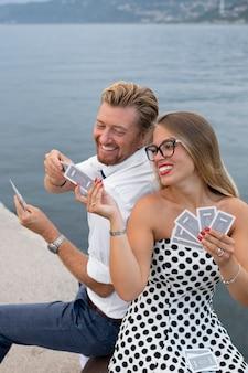 Pessoas sorridentes de tiro médio jogando cartas