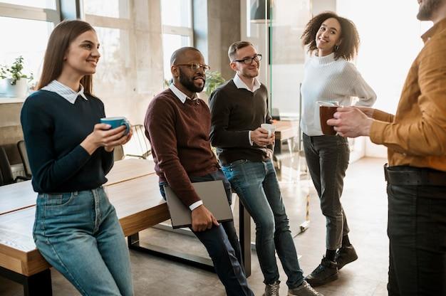 Pessoas sorridentes durante uma reunião com café