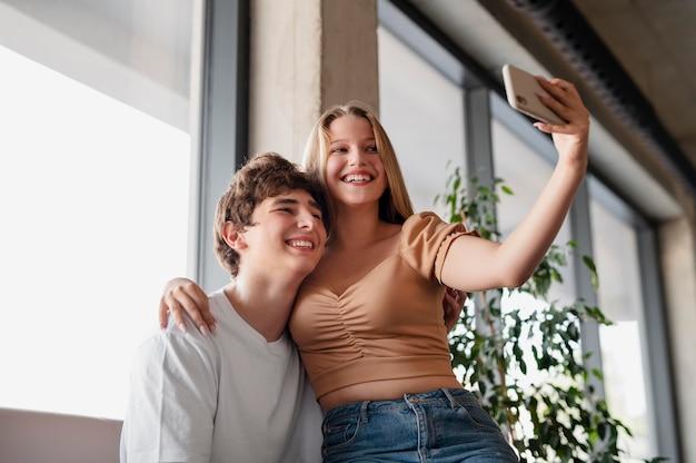 Pessoas sorridentes em tiro médio tirando selfie