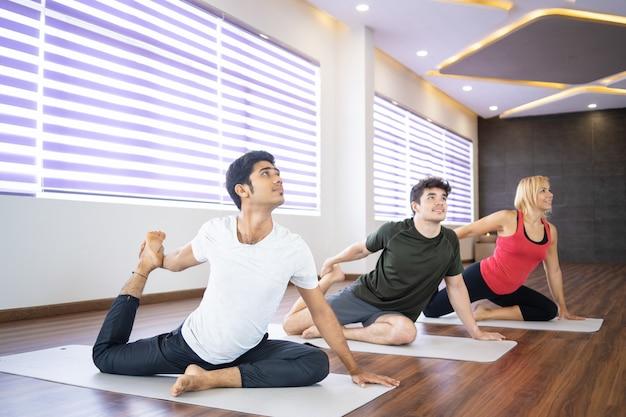Pessoas sorridentes fazendo sereia pose na aula de ioga
