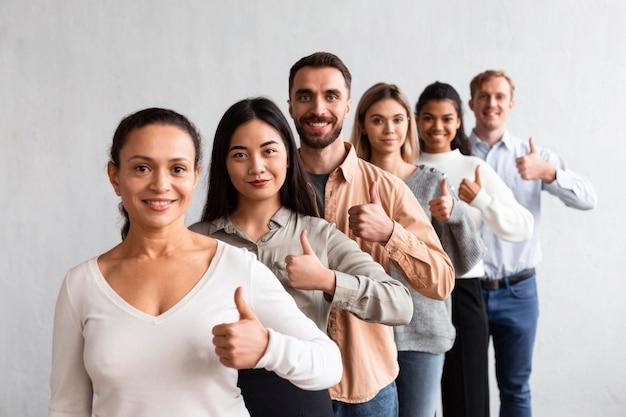 Pessoas sorridentes fazendo sinal de positivo em uma sessão de terapia de grupo