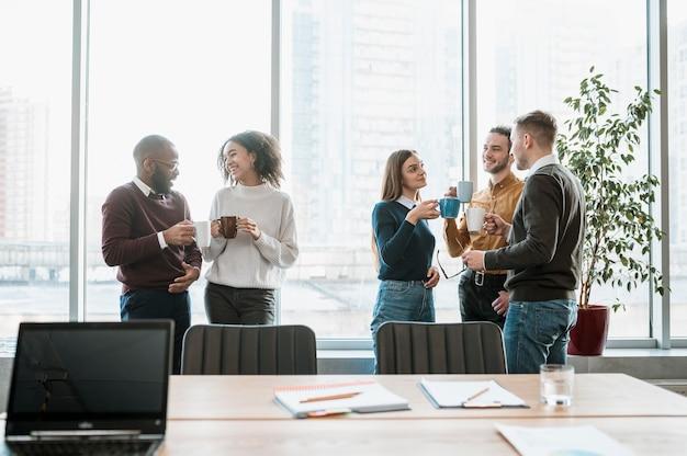 Pessoas sorridentes fazendo uma pausa para o café de uma reunião