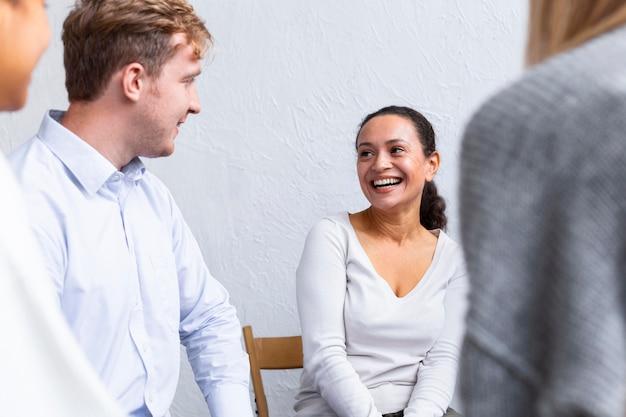 Pessoas sorridentes juntas em uma sessão de terapia em grupo