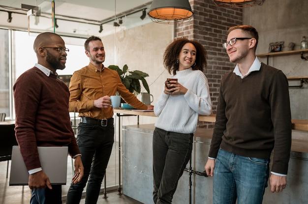 Pessoas sorridentes se encontrando durante uma xícara de café